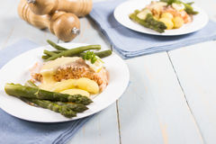Cooked salmon. A cooked salmon fillet served with asparagus new potatoes and green beans Royalty Free Stock Photography