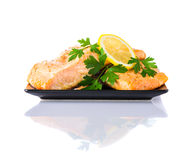 Cooked Salmon Fish Fillet on White Background. Cooked Salmon Fish Filled on Dark Plate with lemon and Parsley leaves isolated on white background Stock Image