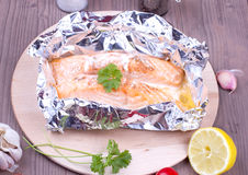 Cooked salmon a foil. On a cutting board Stock Images
