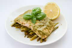 Cooked salmon with garnish. Cooked salmon with pesto, green beans and lemon Stock Photo