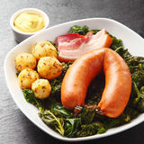 Cooked Sausage, Pork and Potatoes on Leafy Veggies Royalty Free Stock Photos