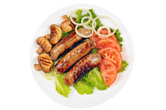 Cooked sausages with green lettuce, tomato, mushrooms and onion on a plate. White background Stock Image