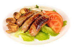 Cooked sausages with green lettuce, tomato, mushrooms and onion on plate. Cooked sausages with green lettuce, tomato, mushrooms and onion on a plate, white Stock Photography