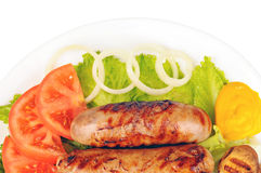 Cooked sausages with mustard, green lettuce, tomato, mushrooms and onion on a plate. White background Stock Photos