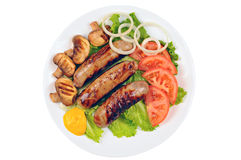 Cooked sausages with mustard, green lettuce, tomato, mushrooms and onion on a plate. White background Royalty Free Stock Photography