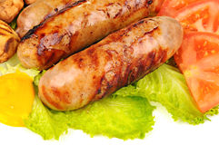 Cooked sausages with mustard, green lettuce, tomato and mushrooms Royalty Free Stock Photos