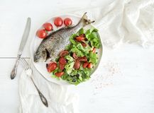 Cooked sea bream fish with fresh vegetable salad Stock Photos