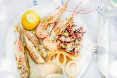 Cooked seafood on plate with lemon and wine. Prawns, squid, octopus, mullet fish and seabream. Traditional Mediterranean dish on Greek island of Kastelorizo Royalty Free Stock Image
