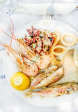 Cooked seafood on plate with lemon and wine Stock Photo