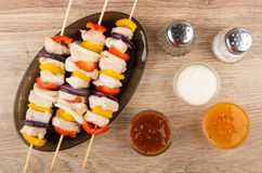 Cooked shashlik in dish, bowls with sauces, pepper and salt Royalty Free Stock Image