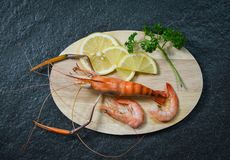 Cooked shellfish seafood shrimps prawns cutting board with herbs and spices on dark background stock image