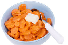 Cooked sliced orange carrots with a dollop of butter. Cooked sliced orange organic carrots topped off with a dollop of butter and served in a blue bowl. There is Royalty Free Stock Images