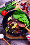 Cooked in spices pork ribs on a black cast-iron frying pan Stock Photo