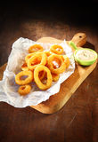 Cooked Squid Rings on Paper Above Serving Board Stock Photo