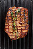 Cooked steak on grill pan. Cooked steak on the grill pan on the steak is herb thyme, top view royalty free stock image