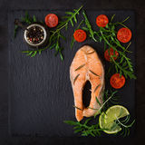 Cooked on steam salmon steak with vegetables. On black background. Dietary menu. Proper nutrition. Top view Royalty Free Stock Image