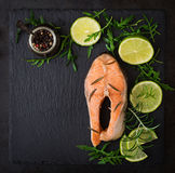 Cooked on steam salmon steak with vegetables. On black background. Dietary menu. Proper nutrition. Top view Stock Image