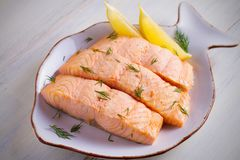 Cooked on steam salmon steaks with lemon. Dietary menu. White plate on white table. Horizontal stock images
