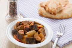 Cooked stewed aubergine pläterar in tjänat som med bröd bordlägger på Arkivbilder