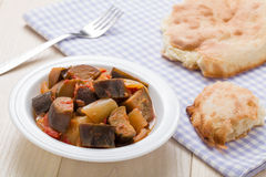 Cooked stewed eggplants in plate served with bread on table Stock Photos