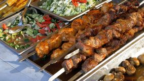 Cooked street food on the store counter. Shish kebabs on skewers, grilled mushrooms, vegetables. Salads. Cook Preparing Delicious Food at Store Market stock footage