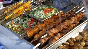 Cooked street food on the store counter. Shish kebabs on skewers, grilled mushrooms, vegetables. Salads. Cook Preparing Delicious Food at Store Market stock video footage