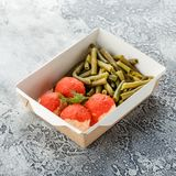 Cooked string beans. Boiled string beans and fish balls in sauce in a lunchbox on a gray background. Healthy food delivery stock photography