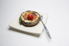 Cooked stuffed portabello mushroom. Stuffed with spinach,mozzarella cheese and sprinked with herbs.Garnished with a  cherry tomato Stock Images