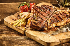 Cooked tbone steak with roasted garlic and tomato. Cooked large t-bone steak and roasted garlic and tomato placed on cutting board over old splintering table royalty free stock photos