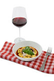 Cooked tortelloni in bowl on napkin by wineglass Stock Image