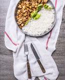 Cooked turkey with delicious rice with parsley in a frying pan on a white napkin with fork knife  wooden rustic background t Stock Photos
