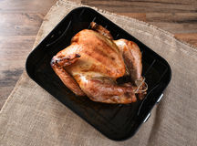 Cooked Turkey in Roasting Pan. High angle view of a cooked turkey in a roasting pan. The golden brown Thanksgiving entree is in a black pan on a burlap table stock photography