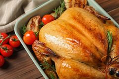 Cooked turkey with vegetables and rosemary in dish on table. Closeup stock photography
