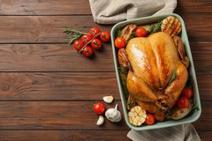 Cooked turkey with vegetables and rosemary in dish on wooden background, flat lay. Space for text stock image