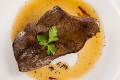 Cooked veal liver steack with sauce on a white plate Stock Photo