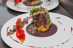 Cooked veal tenderloin. Slow cooked veal tenderloin with morelle mushrooms sauce, red cabbage puree and potatoes gratin Royalty Free Stock Photo