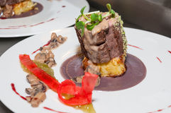 Cooked veal tenderloin. Slow cooked veal tenderloin with morelle mushrooms sauce, red cabbage puree and potatoes gratin on restaurant kitchen royalty free stock photos