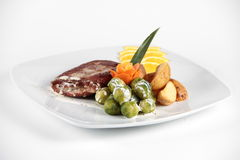Cooked vegetables served with meat on a plate Stock Photography