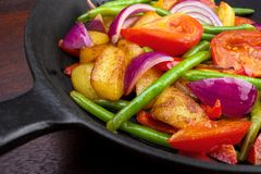 Cooked vegetables. Tomatoes , potatos , red onions and beans on cast iron frying pan closeup Stock Photo
