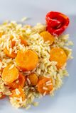 Cooked white rice with carrots and red fried sweet pepper on a white ceramic plate. Vegetarian food. stock image