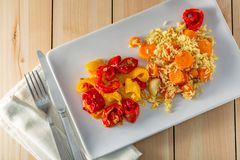 Cooked white rice with carrots and red yellow fried sweet peppers on a white ceramic plate on a wooden table stock photos