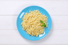 Cooked pearl barley. Cooked whole groats on blue plate Royalty Free Stock Photography
