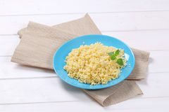 Cooked pearl barley. Cooked whole groats on blue plate Royalty Free Stock Image