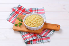 Cooked whole groats. In round baking dish on cutting board royalty free stock photos