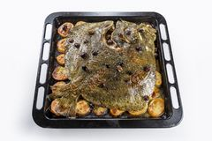 Turbot fish in baking pan oven with potatoes olives and aromatic stock photography