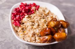 Cooked yummy warm oatmeal and heap of ripe fresh pomegranate seeds and lot of dried dates in white ceramic bowl. On worn gray scratched concrete stock photo