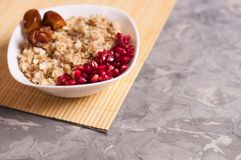 Cooked yummy warm oatmeal and heap of ripe fresh pomegranate seeds and three dried dates in white ceramic bowl. On clean bamboo rug on worn gray scratched royalty free stock photography
