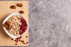 Cooked yummy warm oatmeal and heap of ripe fresh pomegranate seeds and three dried dates in white ceramic bowl. On clean bamboo rug on worn gray scratched royalty free stock image