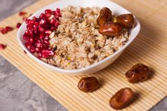 Cooked yummy warm oatmeal and heap of ripe fresh pomegranate seeds and three dried dates in white ceramic bowl stock photography