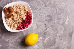 Cooked yummy warm oatmeal and heap of ripe fresh pomegranate seeds and three dried dates in white ceramic bowl. Near whole lemon on worn gray scratched concrete royalty free stock images